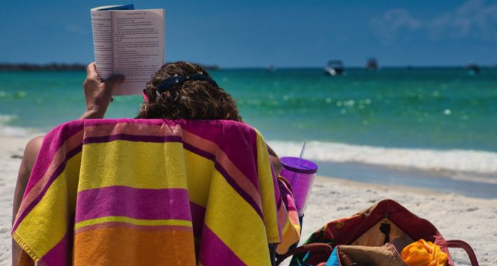 a person reading in a chair in the sand a. the beach https://unsplash.com/photos/MABt_EhXT6E