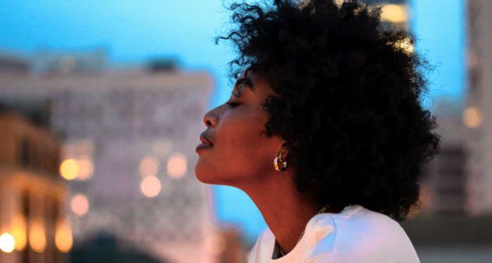 black woman lifting her head against city backdrop https://unsplash.com/photos/BQMZ5ligqps
