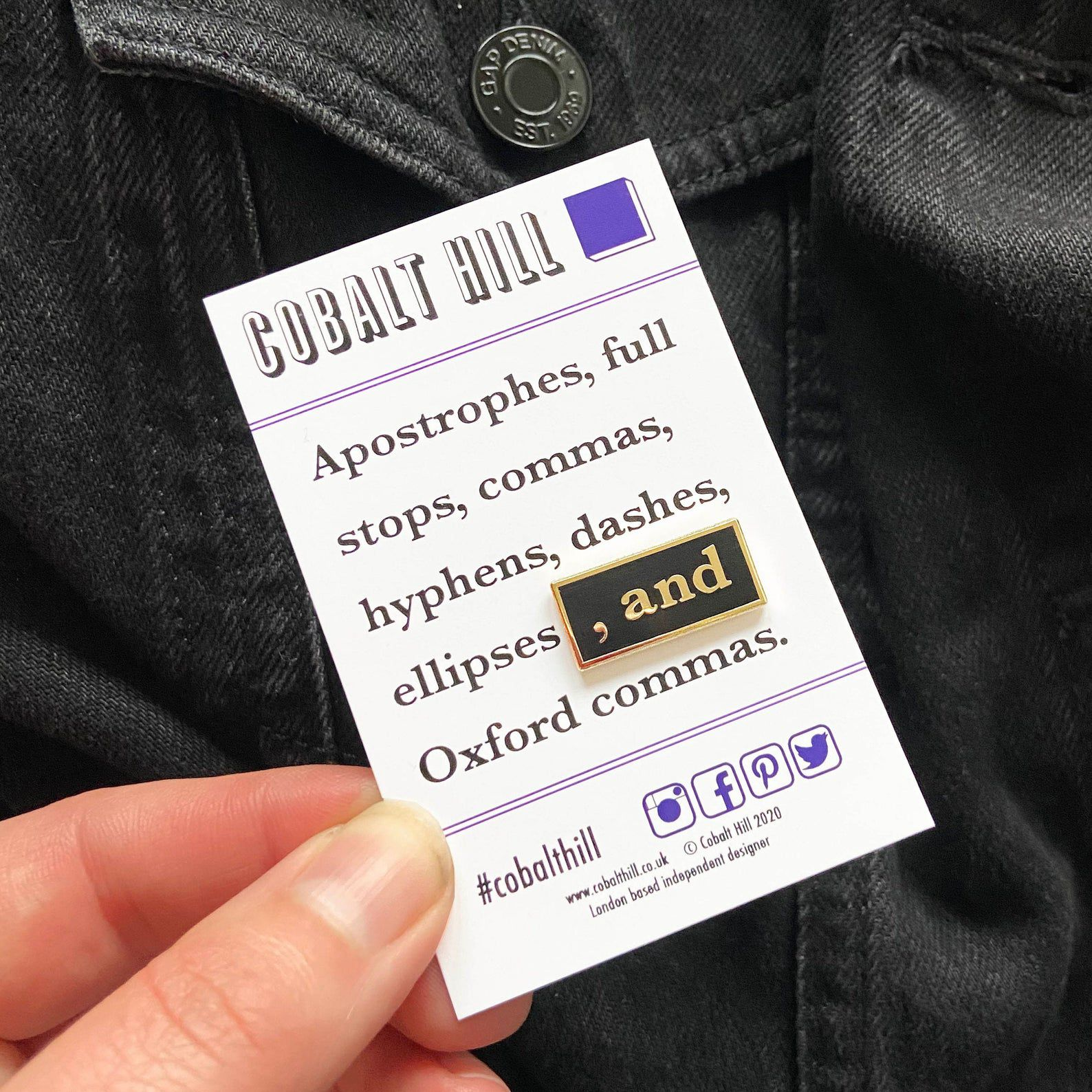 """The pin reads """" , and"""". It is on a cardboard backing that reads """"Cobalt Hill: Apostrophes, full stops, commas, hyphens, dashes, ellipses, and Oxford commas."""""""