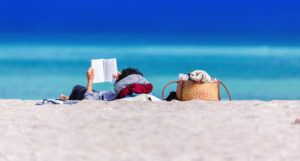 person reading a book on the beach for summer reading and books