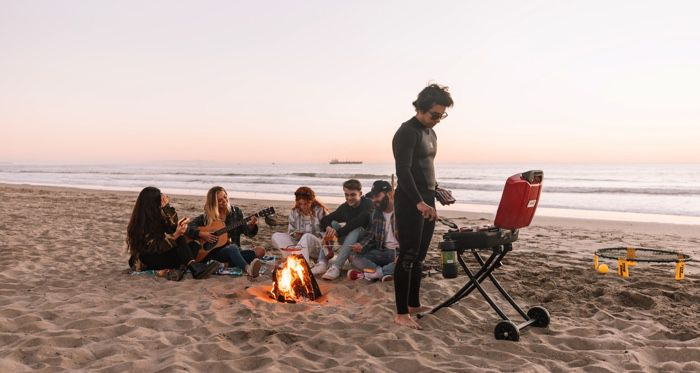 teenagers on the beach with a bonfire and music