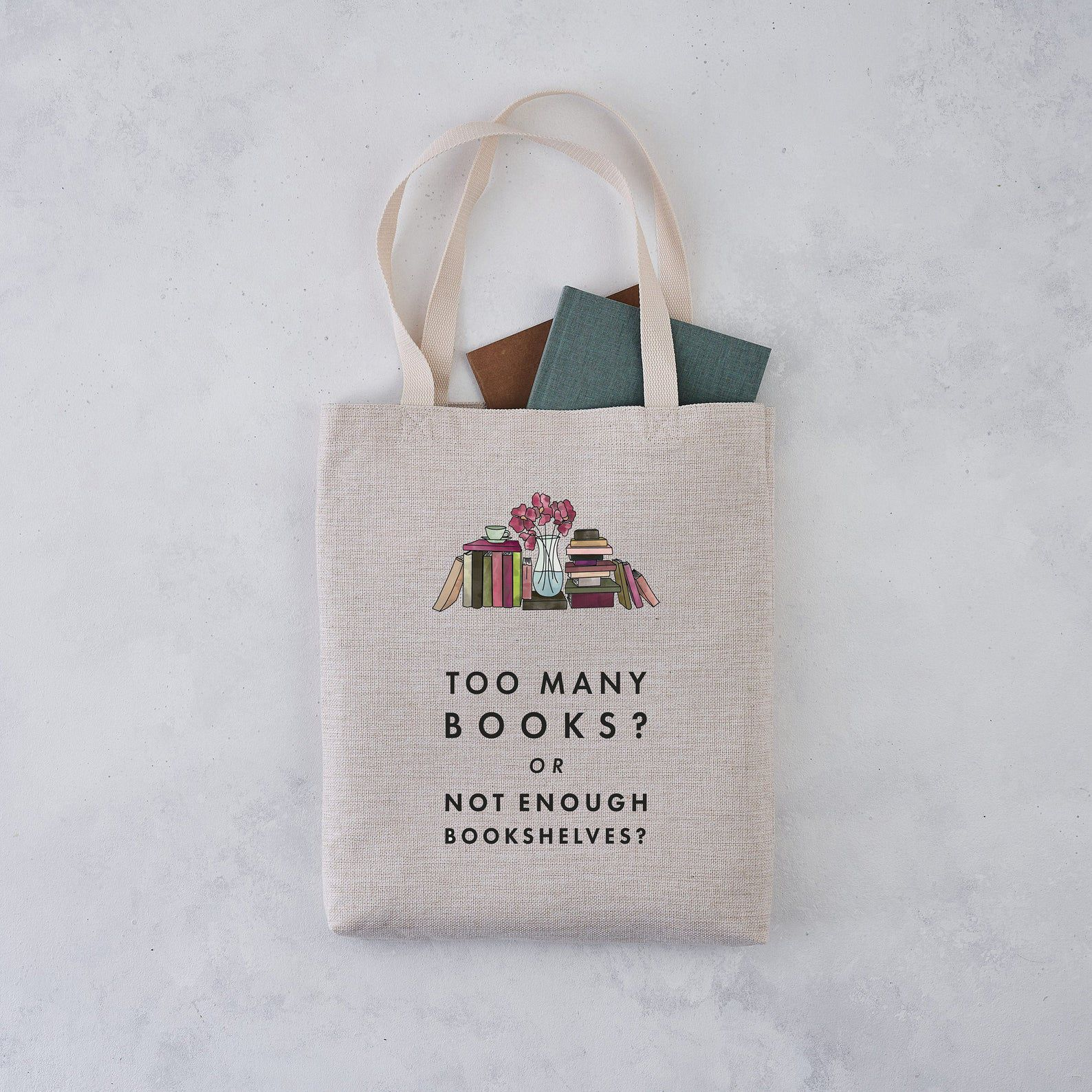 A tote bag with books peeking out rests on a gray background. The tote is light brown in colour and has an image of many books side-by-side and stacked up with a flower vase in the middle. Below, it reads: Too many books? Or not enough bookshelves?