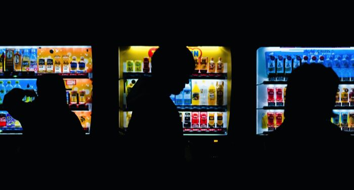 vending machines in a dark room with people congregating