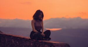 wellness feature of woman sitting on wall at sunset