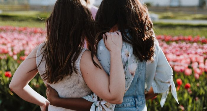 young women or teen girls holding onto each other