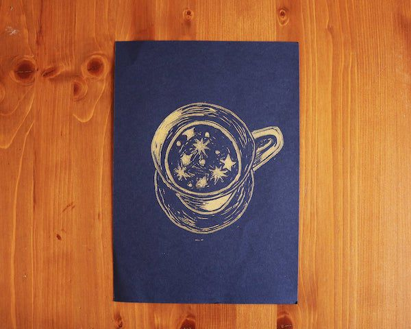 a navy blue print with gold teacup filled with stars sits on a wooden background