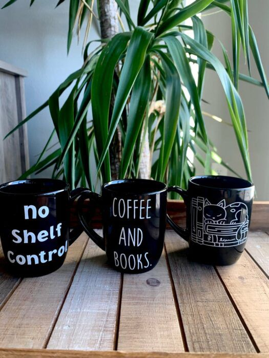 three black mugs with bookish sayings in front of a green plant