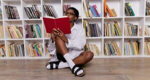 Black woman reading while sitting on the floor