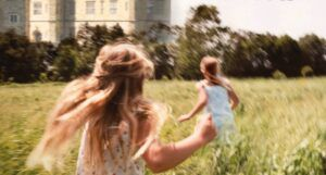 cross section of the cover of I Capture the Castle by Dodie Smith; two girls running through tall grass outside a castle