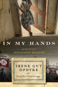 Book cover for In My Hands, showing a woman in a floral dress walking through a door above the title. Beneath the title, nazi flags are visible on a sepia toned street.