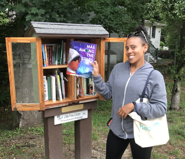 Image of a Black woman holding a book titled Mae Among The Stars in front of a Little Free Library. Image used with permission from Sarah Kamya, founder of Little Free Diverse Libraries