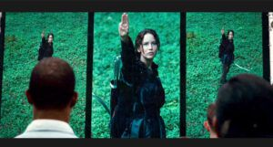 Katniss Everdeen making the three-finger salute in The Hunger Games film