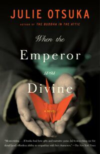 Book cover for When the Emperor was Divine, showing the author's name in orange text over a dark background. Behind the title text, two small hands hold an orange origami crane.