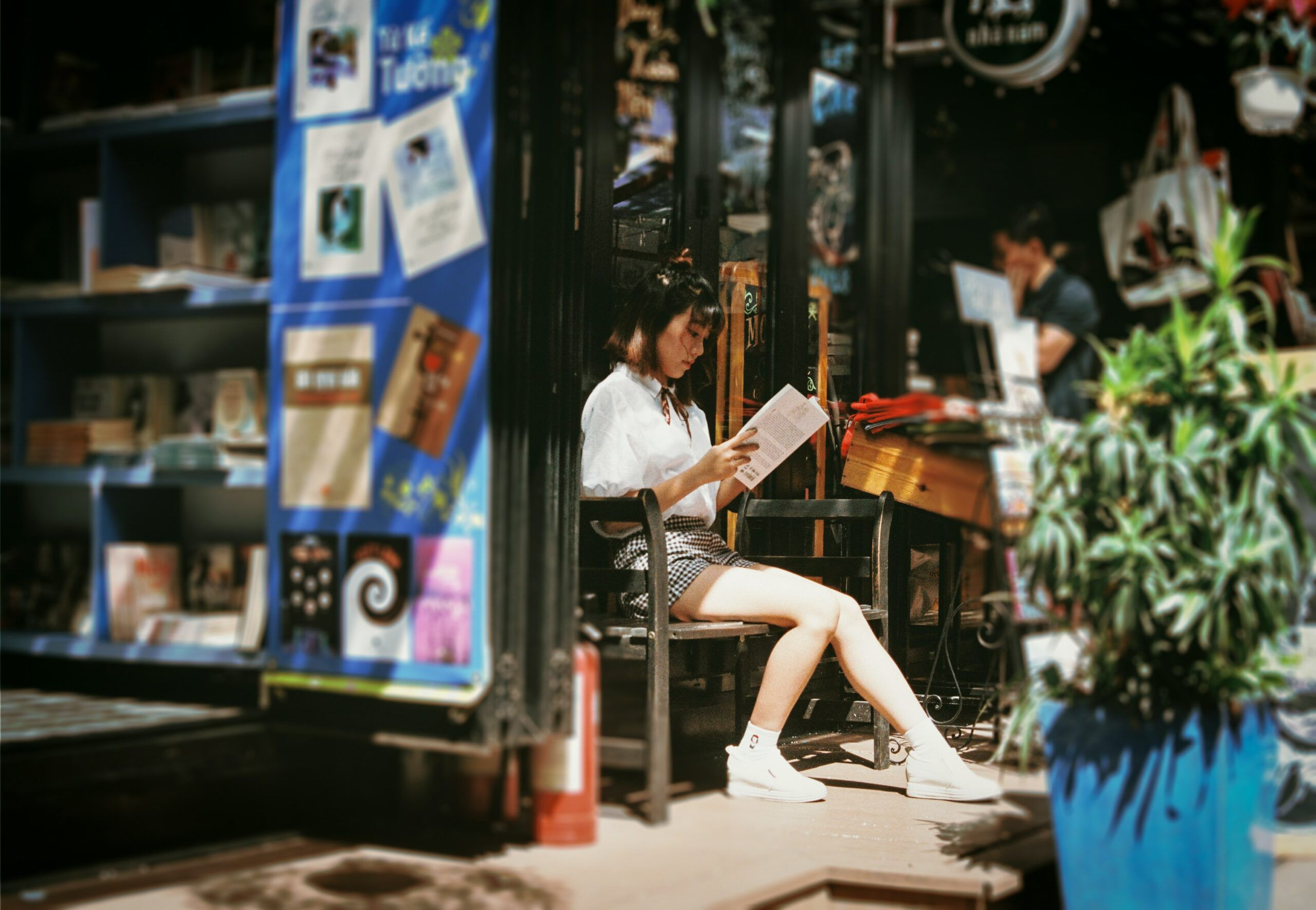 A woman is seen reading a book in front of a bookstore