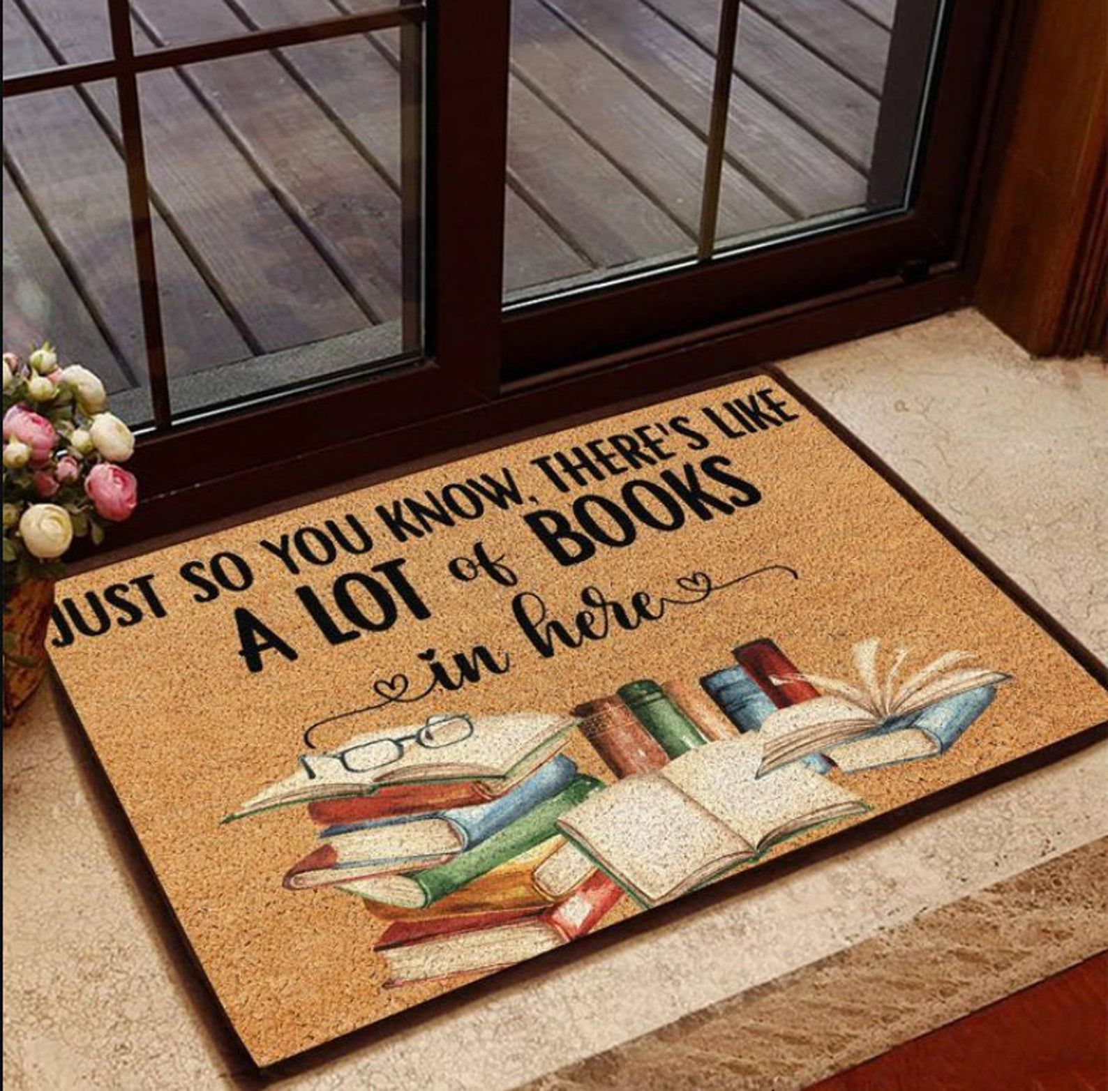"""Brown doormat with black text reading """"Just so you know, there's like a lot of books in here,"""" with a stack of books below."""