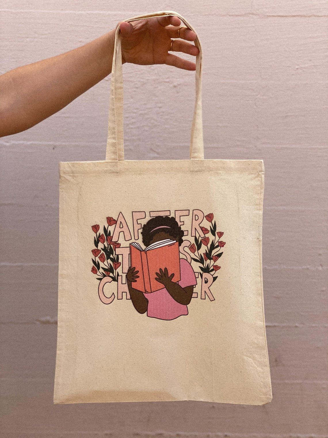 a tote bag with a person holding a book reading in front of the words after this chapter