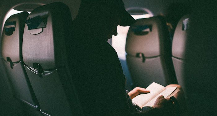 photo of someone reading on an airplane
