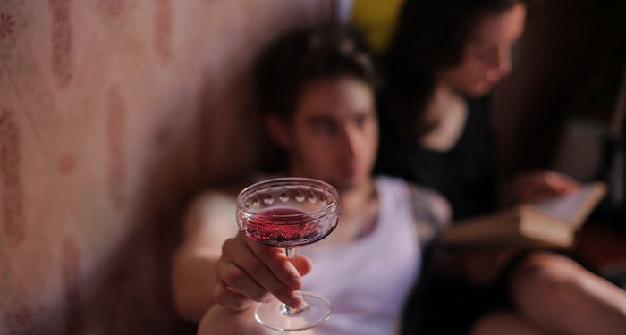 A person holding a drink while an out of focus figure behind them reads