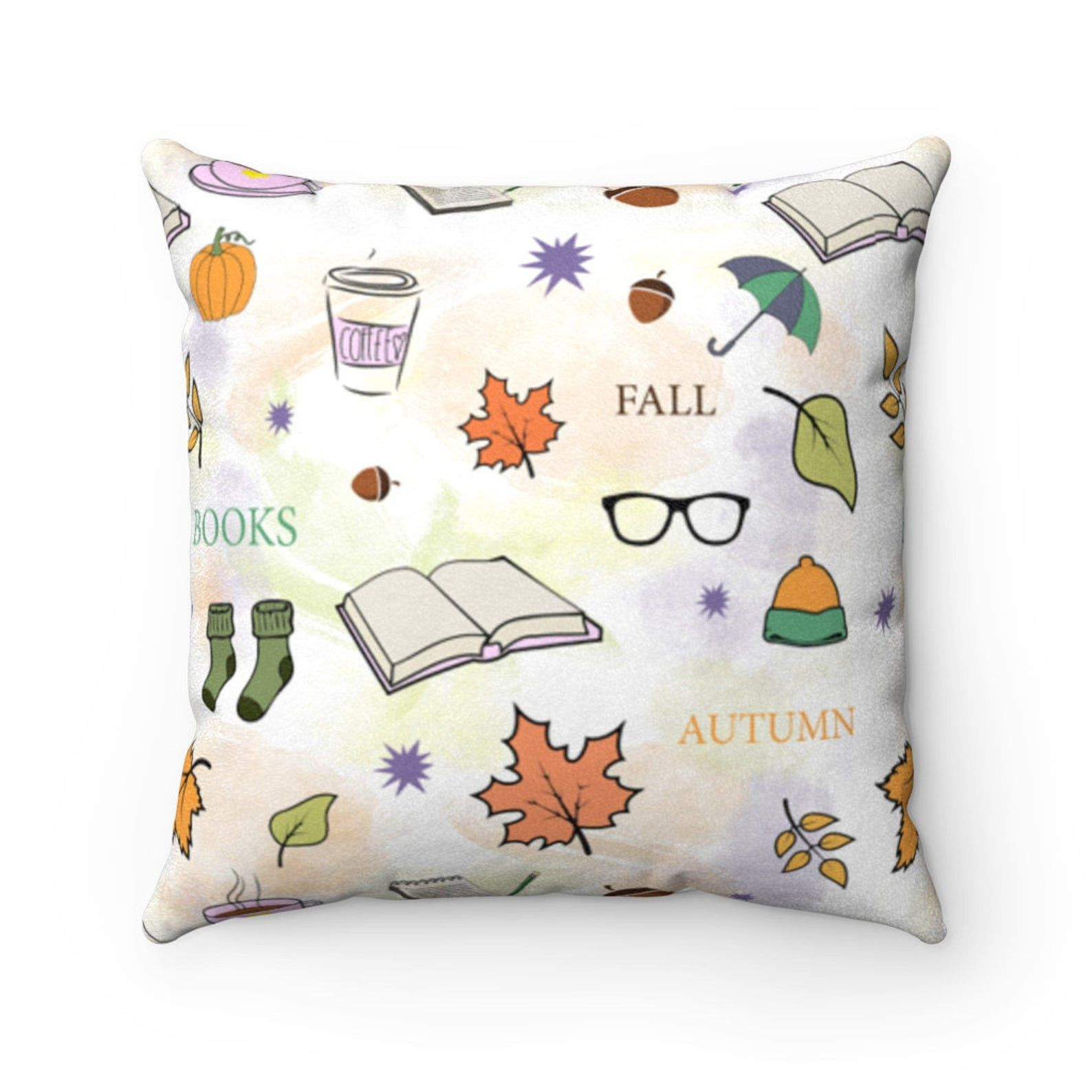 Image of a white throw pillow with fall images, including books, acorns, leaves, and cozy socks.