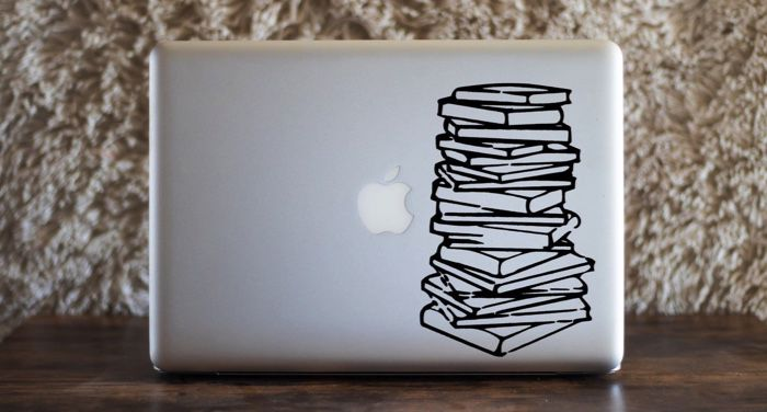 a silver laptop computer with a vinyl book stack decal