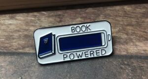 """image of a blue and white """"book powered"""" enamel pin. Design features a book next to a battery life indicator"""