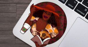 Image of a small sticker depicting a glamorous Black woman in a read hat and yellow floral dress, with a cup of coffee. She's holding a book that is open, and glowing light and fall florals seem to be bursting form the book.