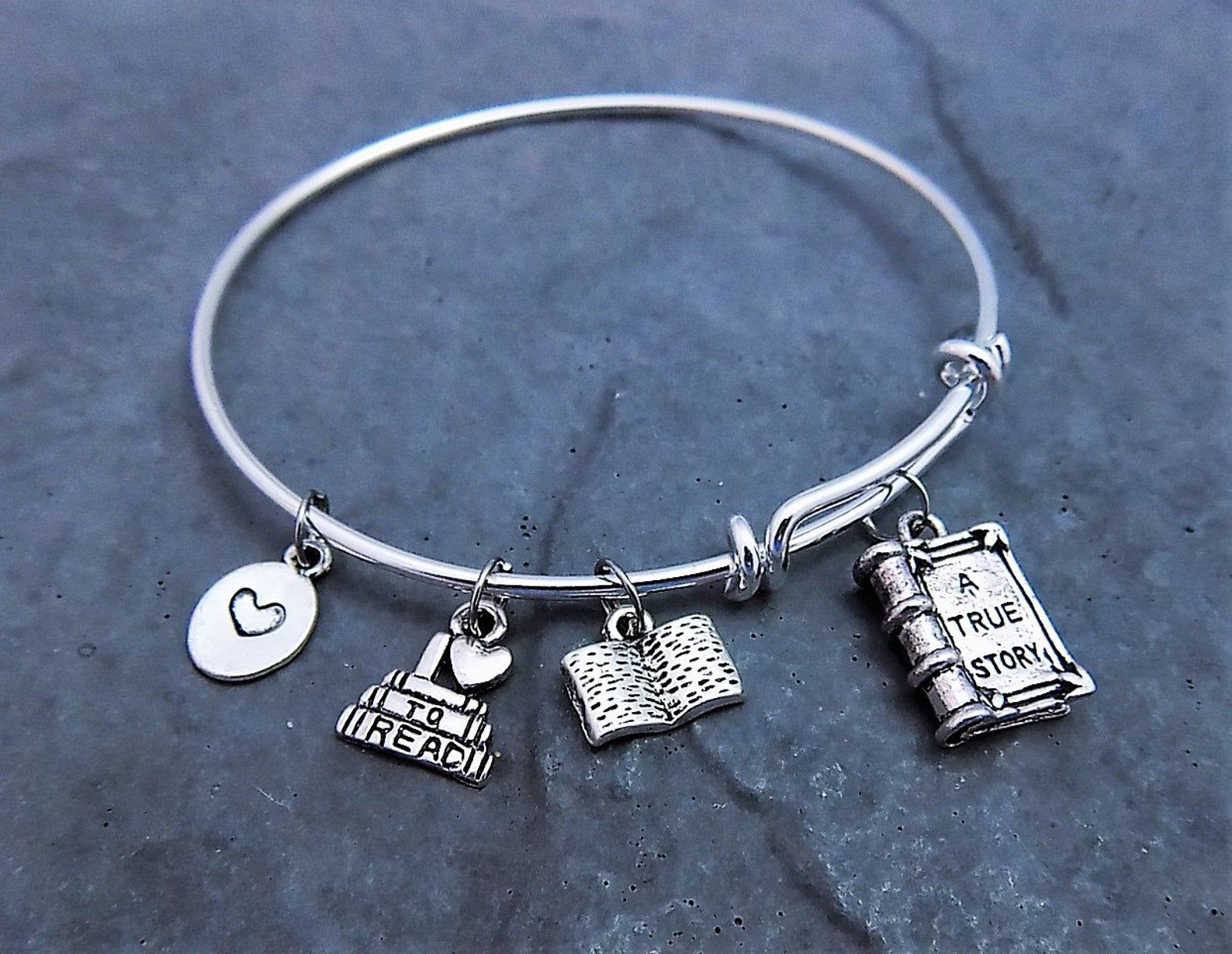a silver booklover charm bracelet with four charms: a heart, a smalll book stack, en open book, ad a closed book without that reads: a true story