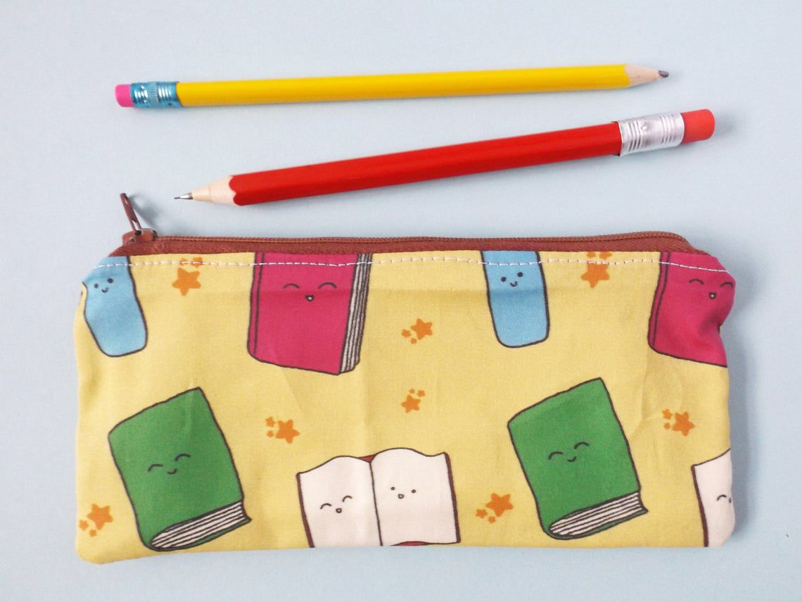 zipper pencil case featuring cartoon books with happy faces
