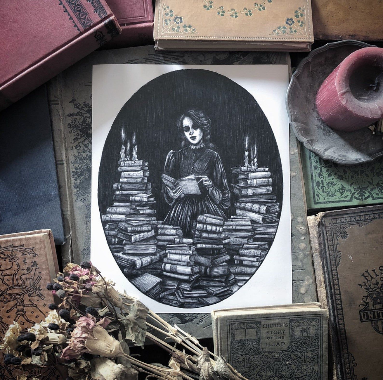 Black and white image of a girl surrounded by books.