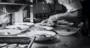 chef bends over to garnish dishes in black and white picture