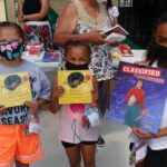 Image of three children at Little Free Library opening ceremony at Wind River