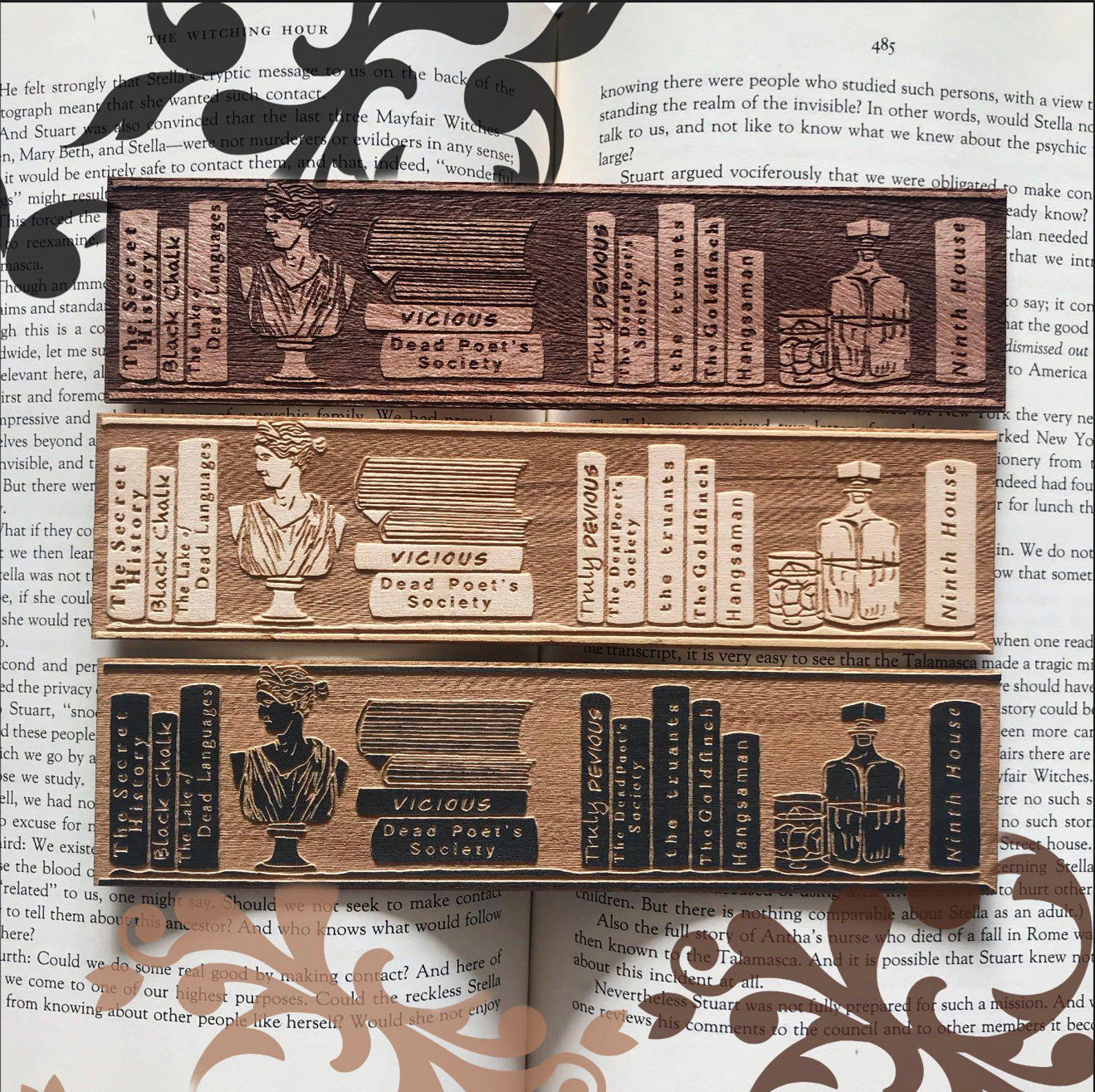 Image of wooden bookmark with bookshelves full of dark academia books.