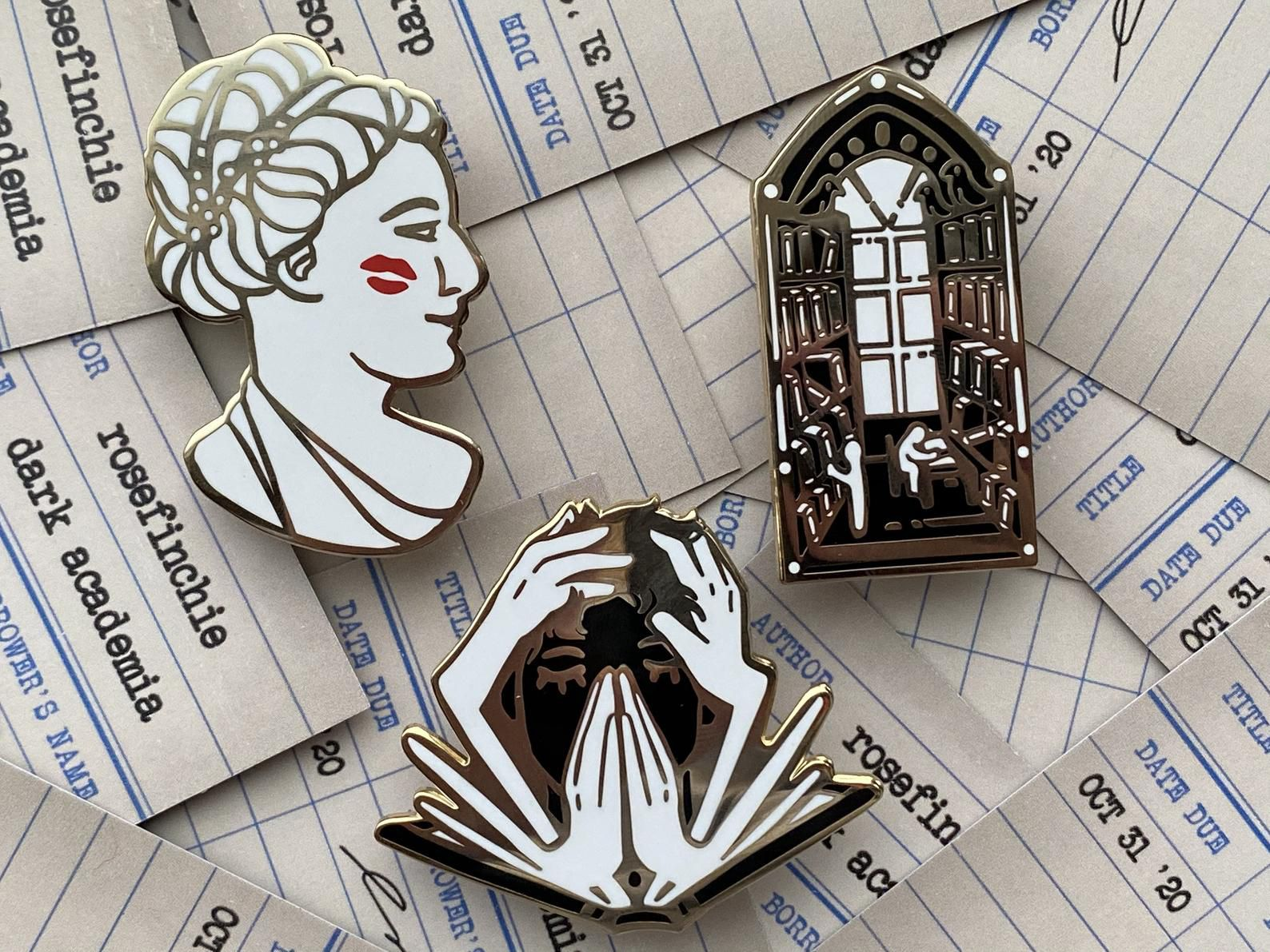 three dark academia enamel pins against a backdrop of library due date cards