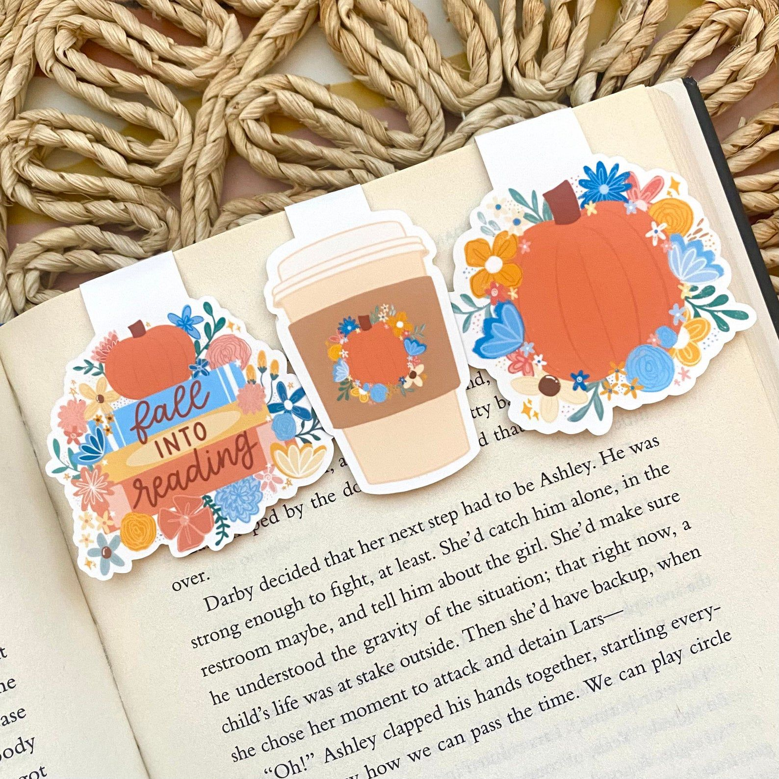 Image of three fall-themed magnetic bookmarks at the top of an open book page.