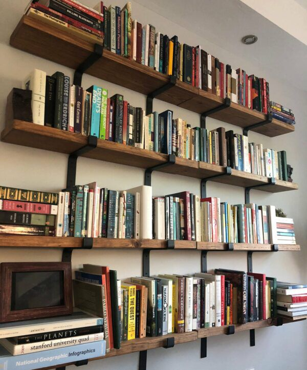 Long wooden wall shelves, filled with books