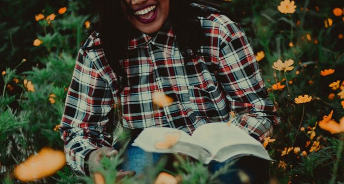 a woman laughing with a book in her lap https://unsplash.com/photos/hzHDduXpHQc