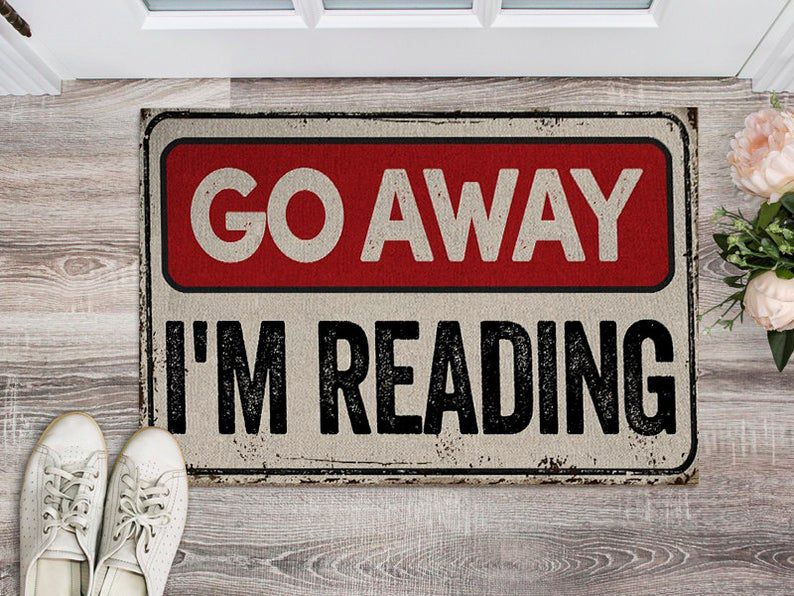 """Image of a doormat that reads """"Go away"""" in red and """"I'm reading"""" in black."""