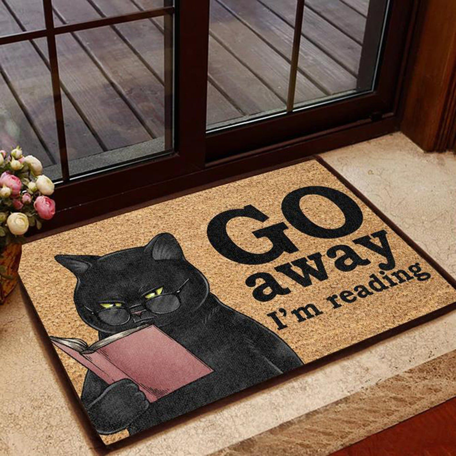 """Image of a black cat reading a book with the text """"Go away I'm reading"""" on a brown doormat."""