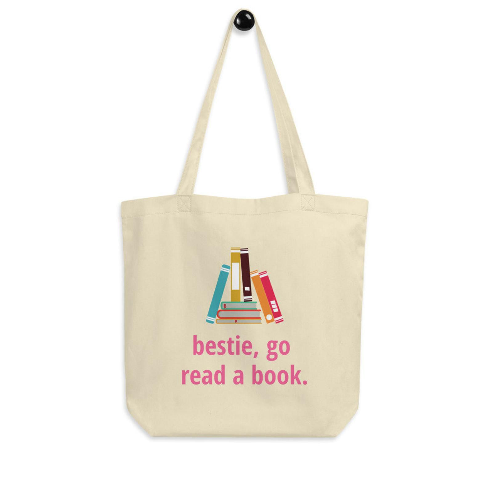 a beige tote bag with a book graphic and text that reads: bestie, go read a book