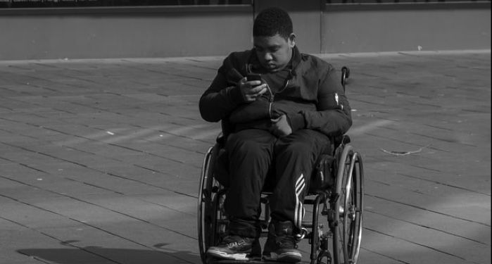 image of grayscale guy sits in wheelchair looking at cell phone