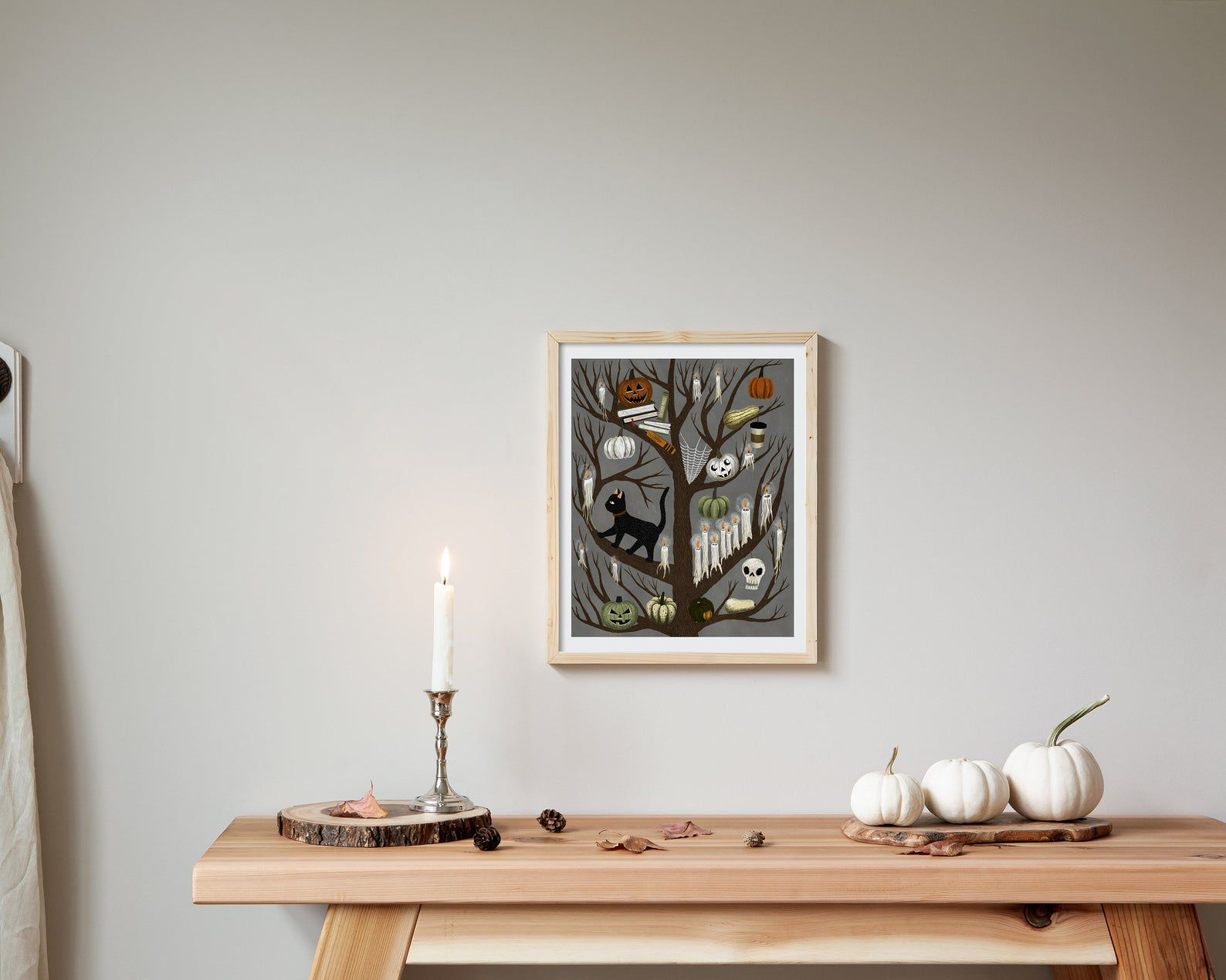 Image of spooky tree art, with branches featuring books, skeletons, ghosts, cats, and pumpkins.