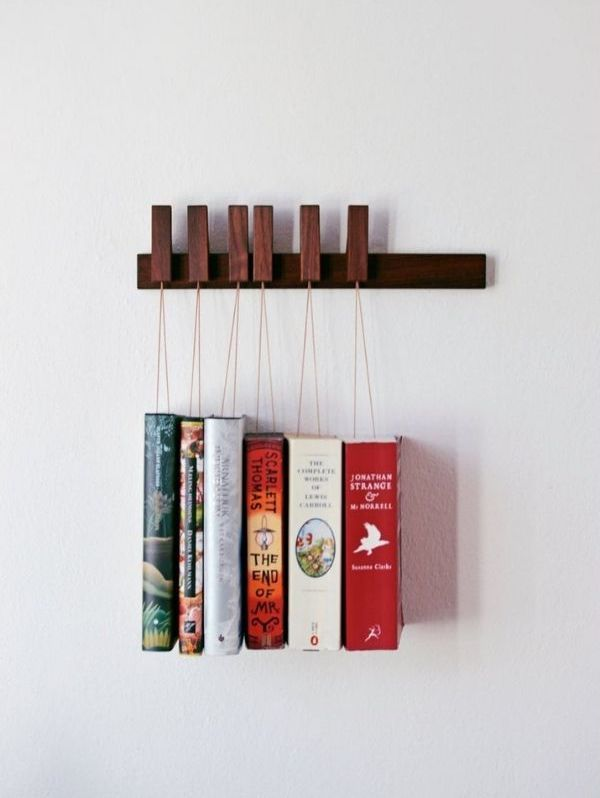 Hanging book rack with books hanging from string attached to pins on wooden ledge