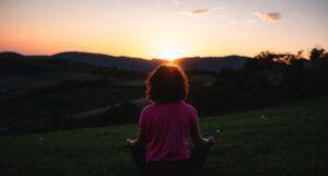 woman sitting cross-legged on grass at sunset https://unsplash.com/photos/WP77TQnwTr4