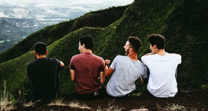 a row of four men sitting on a mountain trail https://unsplash.com/photos/TkrRvwxjb_8