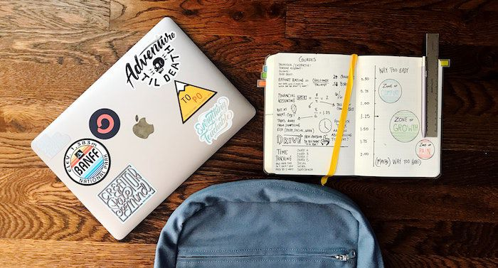 Image of backpack, notebook, and laptop on wood table
