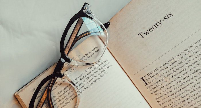 Image of reading glasses on top of an open book