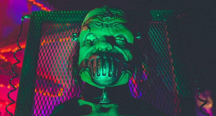 a scary masked figure in front of neon lights