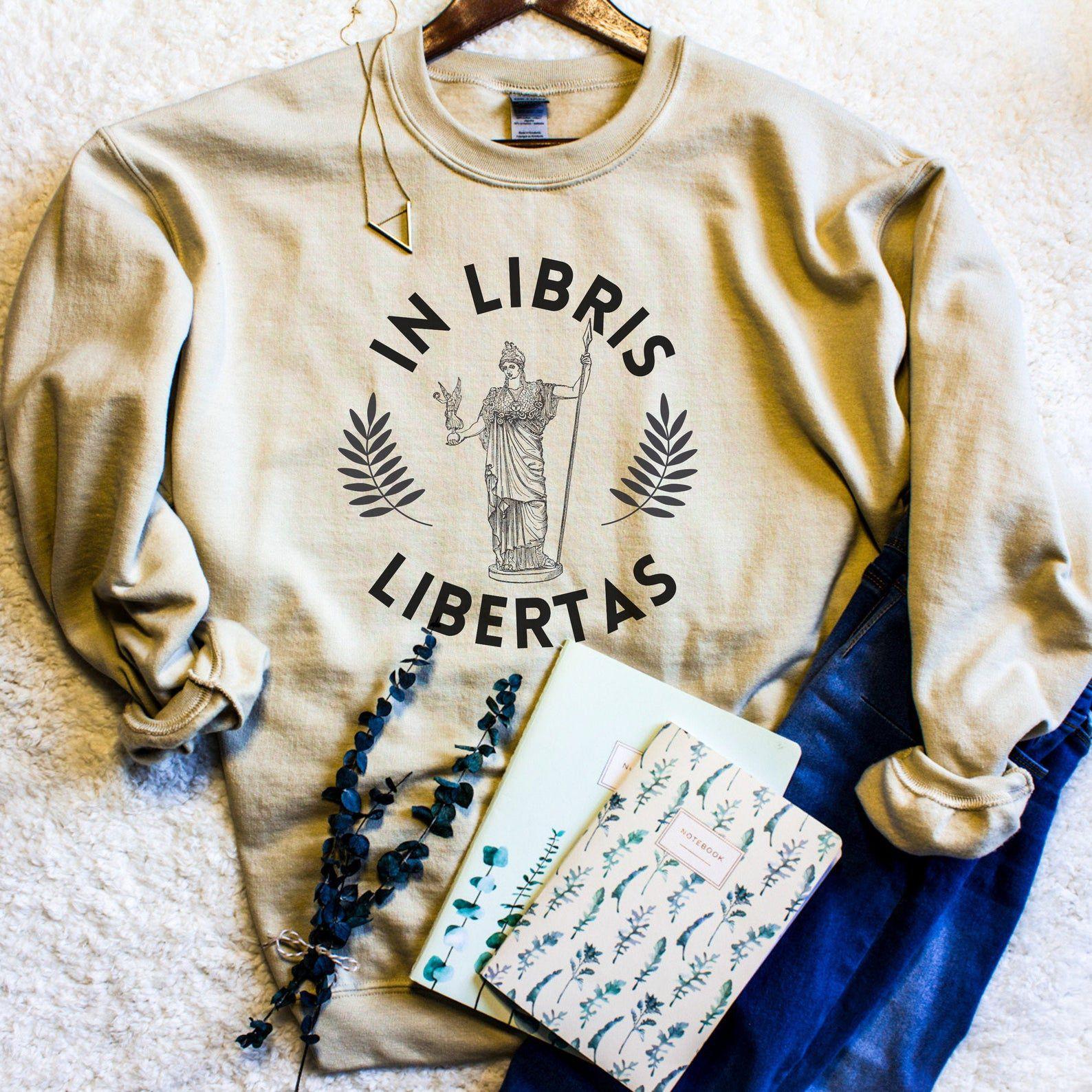 "Image of a cream sweatshirt reading ""In Libris Libertas."""