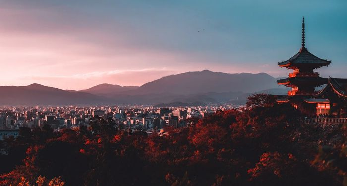 a pagoda surrounded by trees with mountains in the background in Japan https://unsplash.com/photos/E_eWwM29wfU