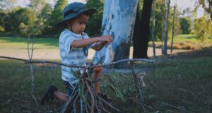 little boy building a fire outdoors for kids camping